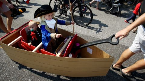 Emma Winkler, 3, points as she re-enacts George Washington's crossing of the Delaware River while being pulled down Carr Avenue in Memphis with her 11-month-old sister, Elizabeth Winkler.