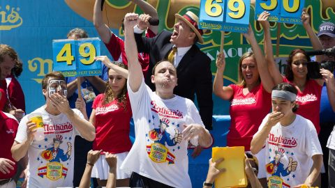 """Perennial chomping champ Joey Chestnut, center, wins <a href=""""http://www.cnn.com/2013/07/04/us/ny-hot-dog-contest/index.html"""">New York's annual Independence Day hot dog eating competition</a> yet again with a total of 69 hot dogs and buns on Thursday at Coney Island in Brooklyn."""