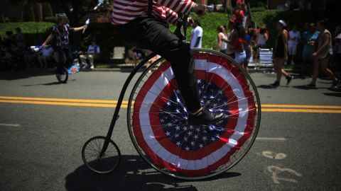 A parade participant rides a penny farthing, or high-wheel bicycle, down the street in Ridgefield Park.