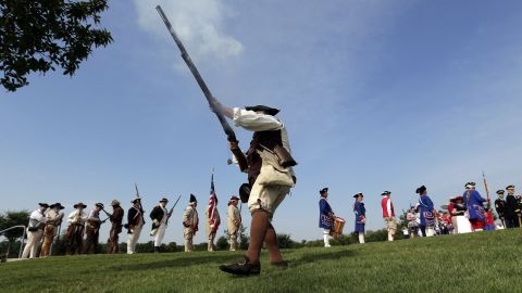 """Ed Lunderman, a member of a Living History Musket Detail, fires his weapon to represent """"the shot heard around the world"""" during a Fourth of July ceremony at Fort Sam Houston National Cemetery in San Antonio."""