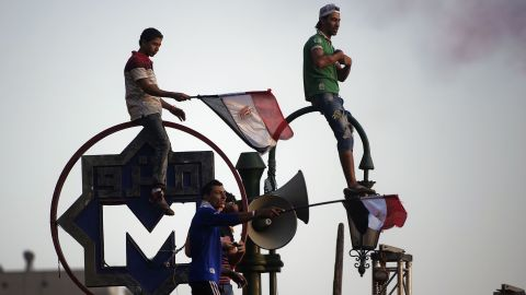 """Egyptians wave the national flag atop of the metro sign in Egypt's landmark Tahrir square on July 4, 2013. Egypt's Muslim Brotherhood, from which ousted president Mohamed Morsi hails, denounced a new """"police state"""" after the arrest of Islamist leaders and the closure of satellite channels. AFP PHOTO/GIANLUIGI GUERCIAGIANLUIGI GUERCIA/AFP/Getty Images"""