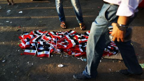 People walk by a pile of Egyptian flags for sale in Tahrir Square on July 4.