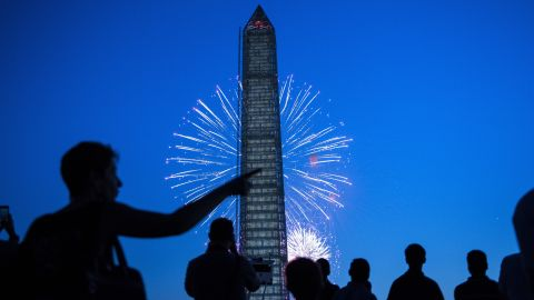 People watch fireworks burst behind the Washington Monument on the National Mall July 4, 2013 in Washington, DC.