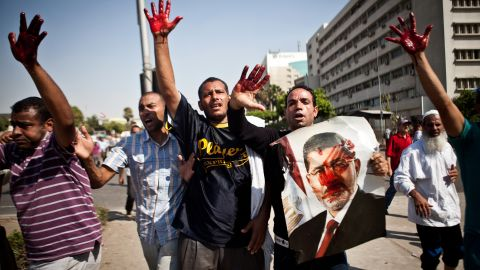 Morsy supporters hold up their bloodstained hands after Egypt's armed forces opened fire on rally in front of the Republican Guard headquarters in Cairo on July 5.