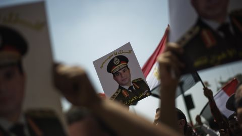 """Egyptians hold portraits of Gen. Abdel-Fatah El-Sisi reading """"Come down, Sisi"""" as they gather in Cairo's landmark Tahrir Square on July 5."""