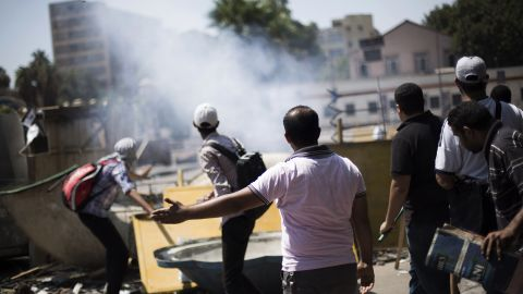 Morsy supporters react to an explosion during clashes with police officers on July 5 outside Cairo University in Giza.