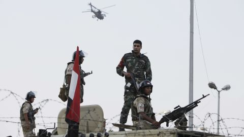 Egyptian Army soldiers stand guard at the Cairo headquarters of the Republican Guard on July 5 as an Apache attack helicopter flies overhead.