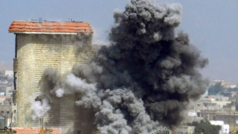 """A handout picture released by the opposition-run Shaam News Network on June 2, 2013, shows smokes rising as a mortar shell hits a building in the town of al-Hula in the Syrian province of Homs during clashes between rebel forces and pro-government troops. UN leader Ban Ki-moon expressed fear for 2,500 """"trapped"""" civilians as Syrian government forces press a campaign to take the city of Homs, a spokesman said."""