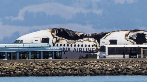 Airport shuttles arrive on the scene after the crash landing.