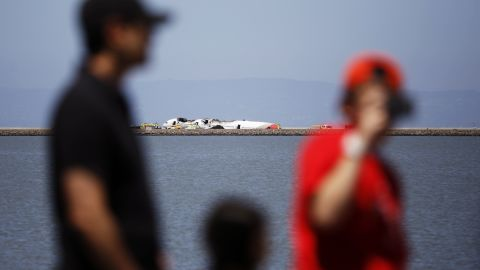 People look over the wreckage across a cove in San Francisco Bay on July 6.