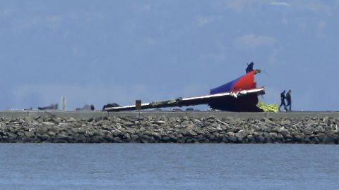 People walk past the wreckage of the plane's tail on July 6.