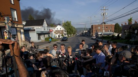 Smoke rises in the background as Quebec Premier Pauline Marois speaks to reporters in Lac-Megantic on July 6.