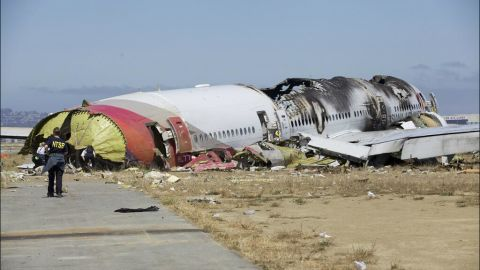 """An investigator stands near the tail of the plane in a handout photo released on July 7. The NTSB has ruled out weather as a problem and said that conditions were right for a """"visual landing."""""""