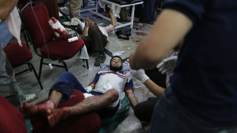 Injured men receive medical attention after clashes between supporters of Morsy and security forces in Cairo on July 8.