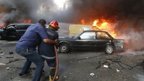A firefighter is helped as he extinguishes fire at the site of an explosion in Beirut's southern suburb neighbourhood of Bir al-Abed on July 9, 2013.