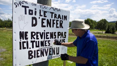 """Andre Blais adjusts a sign erected near the train tracks. It bears a message for the rail company: """"Shame on you MMA.""""  It is signed """"The population"""" and refers to the """"train from hell."""""""