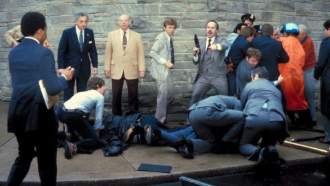 A barrage of Secret Service agents holds down Hinckley and tends to the wounded.