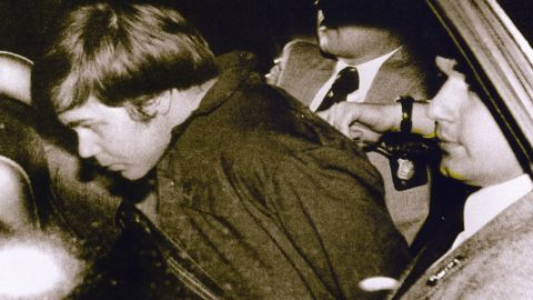 """Hinckley is escorted by police following his arrest.  He was obsessed with actress Jodie Foster, haven written to her from his hotel room earlier that day, """"There is a definite possibility that I may be killed in my attempt to get Reagan."""" Hinckley wrote he was doing this to try to win her love."""