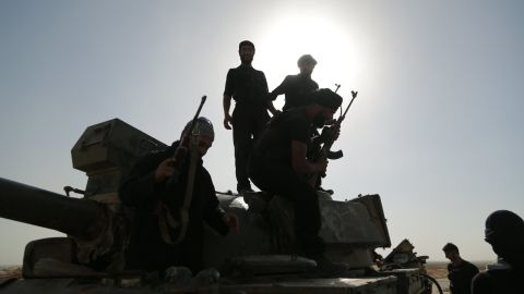 Syrian rebels inspect a tank left behind by government forces in the outskirts of Raqqa on July 1, 2013.