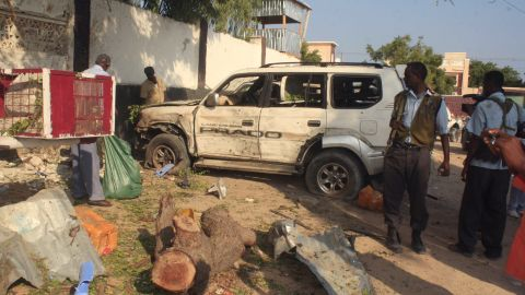 """Despite the relatively peaceful business environment, insurgents still launch sporadic attacks. Jamal's restaurants have also been targeted. Pictured, Somali security forces stand near the debris left after two suicide bombers attacked one of """"The Village"""" restaurants on November 3, 2012."""