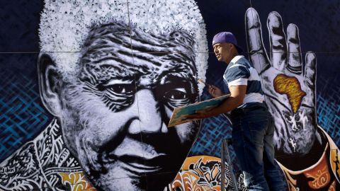 """South African artist John Adams works on a giant painting of Nelson Mandela in a suburb of Johannesburg. Mandela, an anti-apartheid icon and Nobel peace laureate, endured 27 years in prison before becoming South Africa's first democratically elected president. Click through the gallery for other artistic tributes to """"the world's most famous political prisoner."""""""