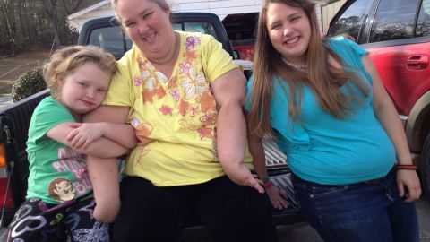 Honey Boo Boo (Alana Thompson), Mama (June Shannon), and Chubbs (Jessica Shannon) sitting on a pickup truck bed.