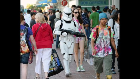 """Myke Soler walks outside the San Diego Convention Center dressed as a """"Star Wars"""" stormtrooper with his wife during Comic-Con International 2013 on Wednesday, July 17, in San Diego, California.  Started in 1970, the event is estimated to bring well over 100,000 attendees."""