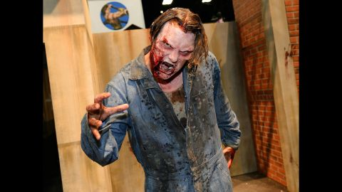 """A zombie character poses at """"The Walking Dead"""" booth."""