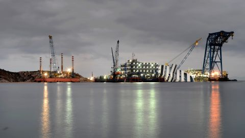 Cranes and floating decks surrounding the ship light up the dusk sky on January 9, 2013.