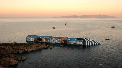 A bird flies overhead the Costa Concordia on January 18, 2012. Rescue operations were suspended as the ship slowly sank further into the sea.