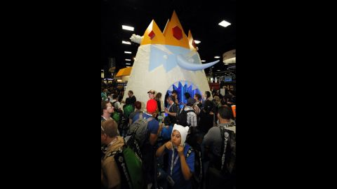 """Fans wait to walk through a giant display of Ice King character from """"Adventure Time"""" at the Cartoon Network booth during the Preview Night event."""