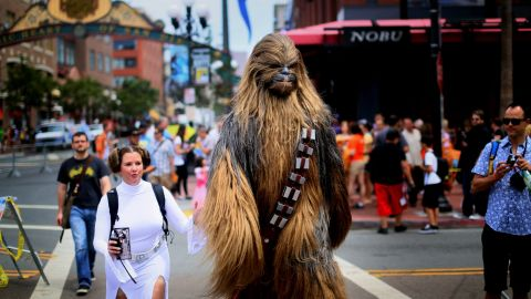 """Fans dressed as """"Star Wars"""" characters Princess Leia and Chewbacca walk down San Diego's 5th Avenue."""