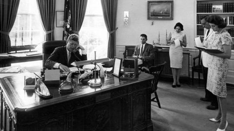 Thomas, third right, takes notes as President John F. Kennedy speaks on the phone in the Oval Office on August 23, 1962.