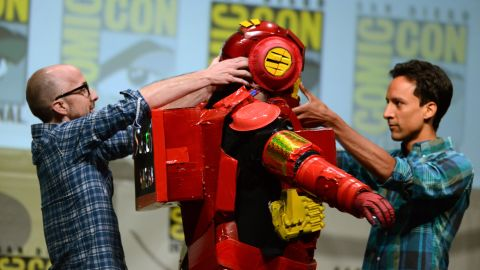 """Dan Harmon, center, creator and executive producer of """"Community,"""" is helped out of a costume by actors Jim Rash, left, and Danny Pudi during the """"Community"""" panel on the final day of Comic-Con International on Sunday, July 21, in San Diego. Running from Wednesday through Sunday, July 21, the event floods the San Diego Convention Center with more than 100,000 attendees as they shuffle between panels promising exclusive previews and answers to fans' burning questions. See more sights from Comic Con 2013."""