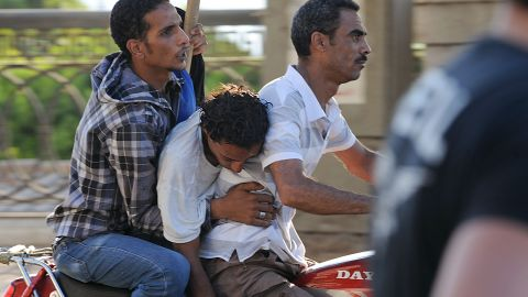 Men evacuate an injured opponent of Morsy during clashes with his supporters in Cairo on July 22.
