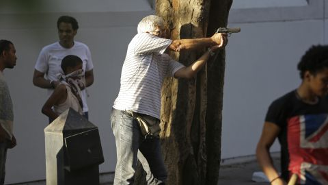 A man fires a gun during clashes between opponents and supporters of Morsy in Cairo on July 22.