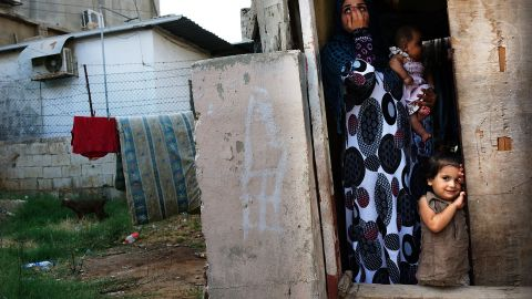 A Syrian refugee family from the Deir el Zour, Syria pauses in their doorway in a neighborhood with a high concentration of Syrian refugees on July 01, 2013 in Beirut, Lebanon.