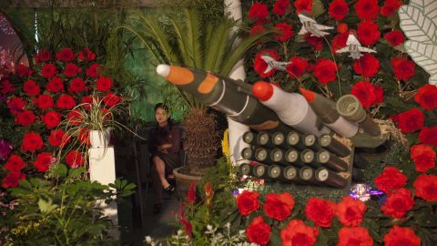 """A woman sits next to models of military weapons at a festival for the """"Kimilsungia"""" and """"Kimjongilia"""" flowers, named after the country's late leaders, on Wednesday, July 24, in Pyongyang, North Korea. The exhibition was held to mark the 60th anniversary of the signing of the armistice agreement that ended the fighting on July 27, 1953."""