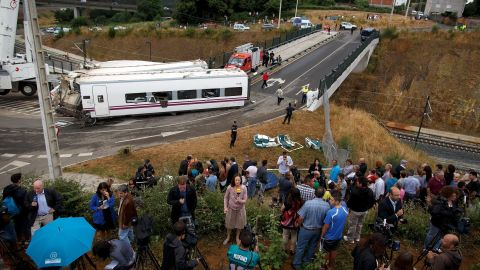 SANTIAGO DE COMPOSTELA, SPAIN - JULY 25: TV Journalists report from a vegetable plot near a train crash that killed at least 80 people on July 25, 2013 at Angrois near Santiago de Compostela, Spain. The crash occurred as the train approached the north-western Spanish city of Santiago de Compostela at 8.40pm on July 24th, at least 80 people have died and a further 131 reported injured. The crash occured on the eve of the Santiago de Compostela Festivities. (Photo by Pablo Blazquez Dominguez/Getty Images)