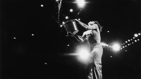 Jagger empties a bucket of water on stage at the 1976 Knebworth Festival in Hertfordshire, England.