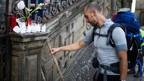 A man leaves his cane next to candles in memory of the train crash victims on Friday, July 26, in Santiago de Compostela.