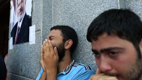 Two men mourn Morsy supporters who were killed in overnight clashes with security forces, in Cairo, on July 27.
