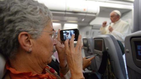 """A journalist takes a picture of Pope Francis during the press conference on the flight back to Italy. The pope said the role of women in the church should be deeper, but he brushed aside the possibility of women being ordained as priests. """"The church says no. That door is closed."""""""