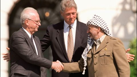 US President Bill Clinton (C) stands between PLO leader Yasser Arafat (R) and Israeli Prime Minister Yitzahk Rabin (L) as they shake hands on September 13, 1993, at the White House in Washington DC. Rabin and Arafat shook hands for the first time after Israel and the PLO signed a historic agreement on Palestinian autonomy in the occupied territories.