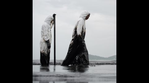 Thai navy workers move through the sludge on July 30.
