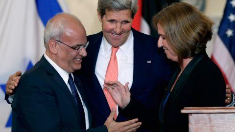 John Kerry (C) looks on as Israeli Justice Minister Tzipi Livni and Palestinian chief negotiator Saeb Erekat (L) shake hands.