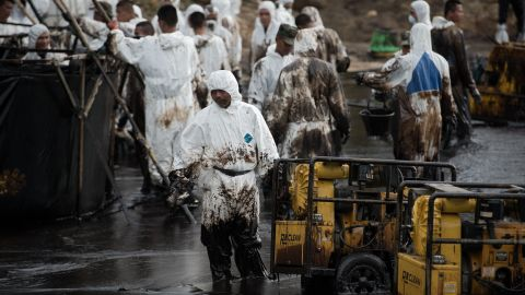 Thai navy personnel are splattered with oil as they work to clean up Ao Phrao beach on July 30.