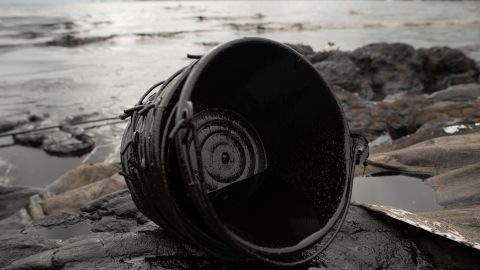 An oil-stained bucket used in clean-up efforts lies on Ao Phrao beach on July 30.