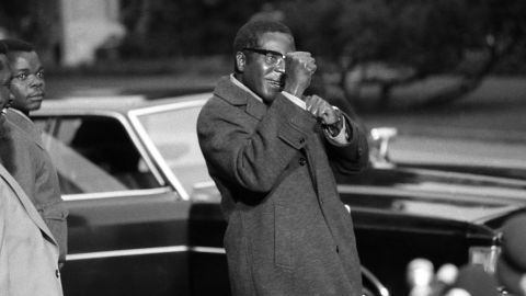 Mugabe gestures towards the media in Geneva, Switzerland, at a 1974 conference convened to address the civil war in Rhodesia. After being imprisoned for 10 years in Rhodesia, Mugabe attended the peace talks as a leader of the guerrilla movement ZANU-PF (Zimbabwe African National Union-Patriotic Front). Rhodesia was the state that eventually became Zimbabwe.
