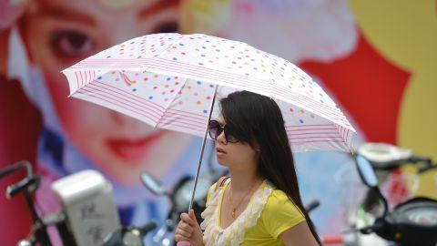 A woman uses an umbrella as sun protection  as a heatwave hits Shanghai on Thursday, July 4.